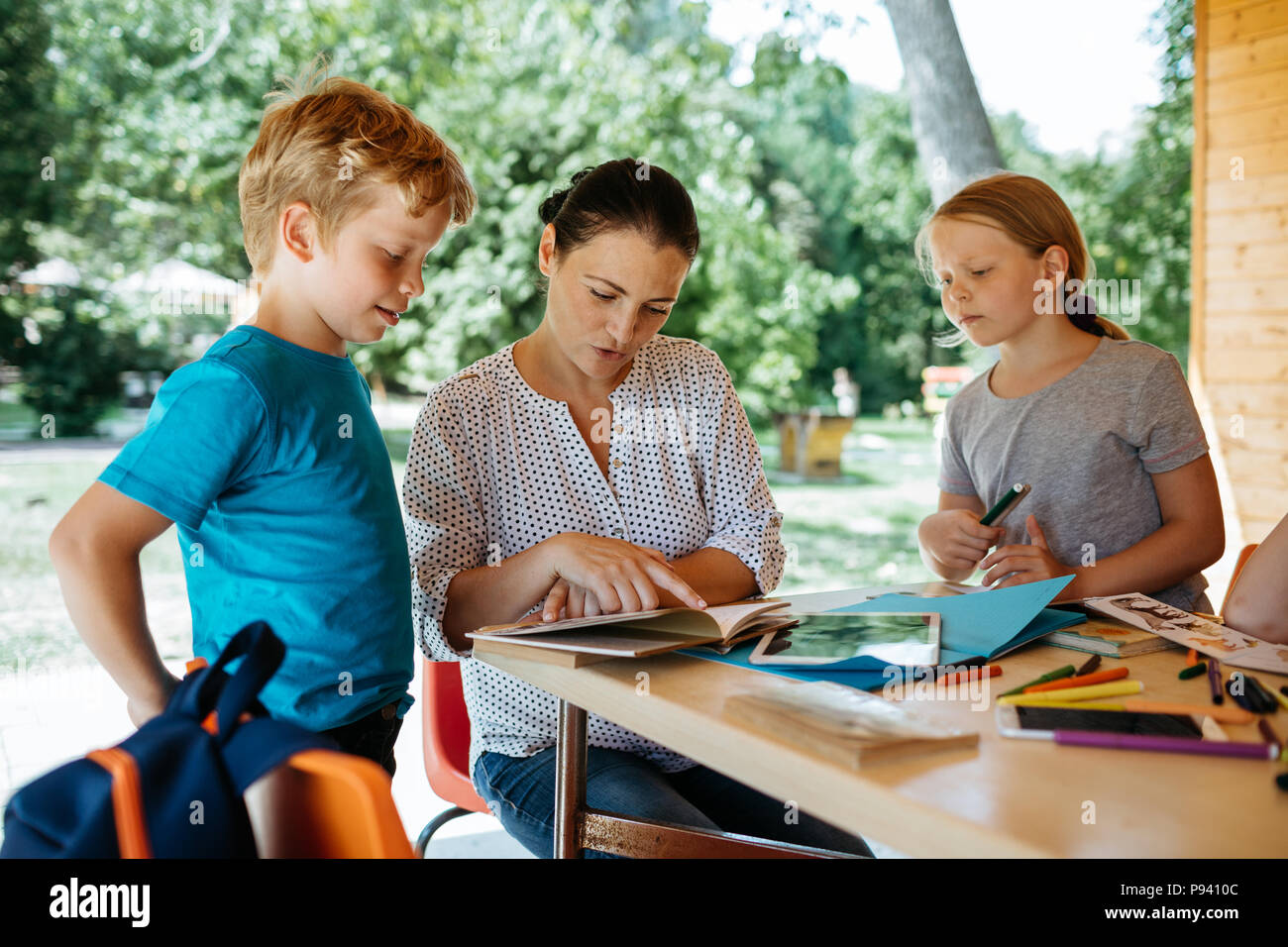 Schoolchildren learning with a teacher and listening to her. Teacher explaining to children. - Stock Image