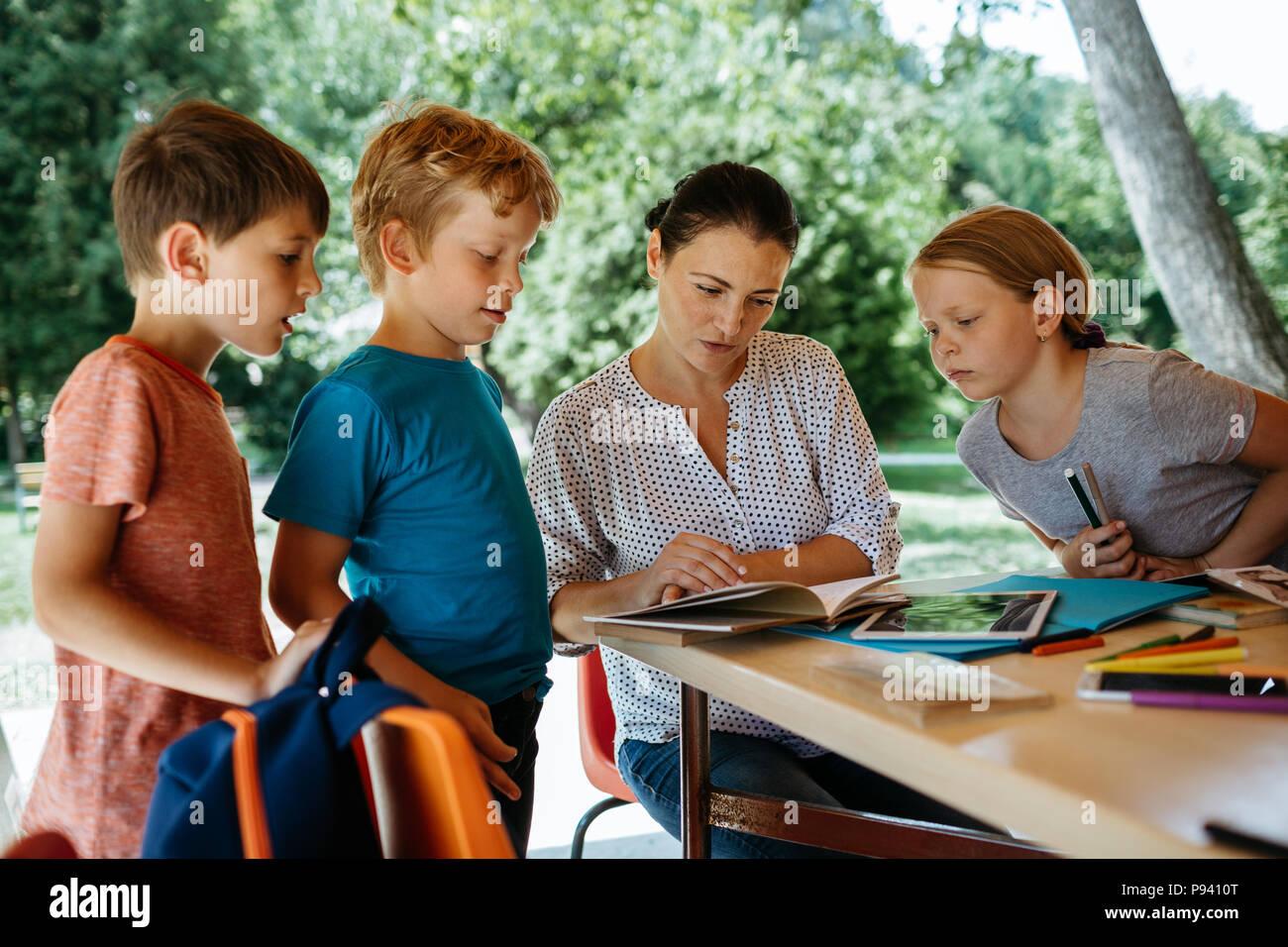 Schoolchildren engaged in listening to a teacher. Teacher explaining to children. - Stock Image