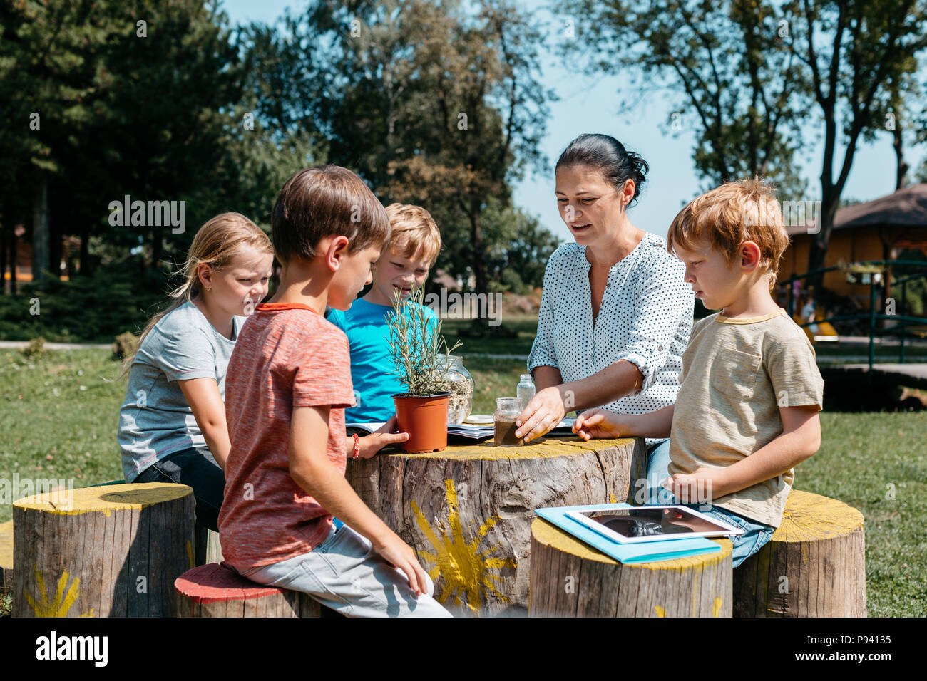 Group of schoolchildren having a lesson outside in a park. Children sitting around a wooden table and learning together with a teacher in the garden. - Stock Image