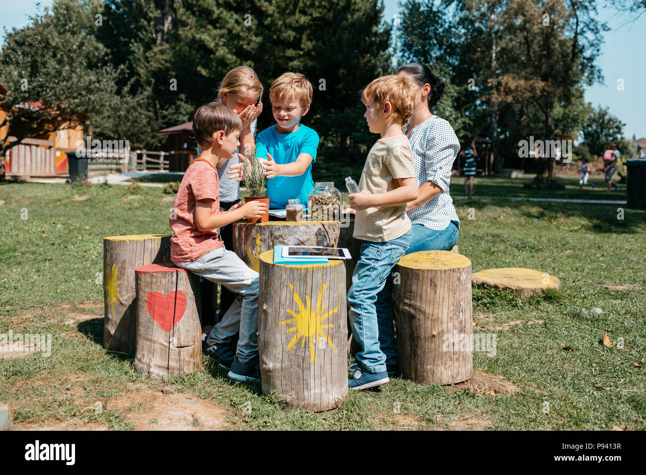 Group of young schoolchildren having a lesson outside in a park. Young primary students exploring herbs through their senses in a garden. - Stock Image