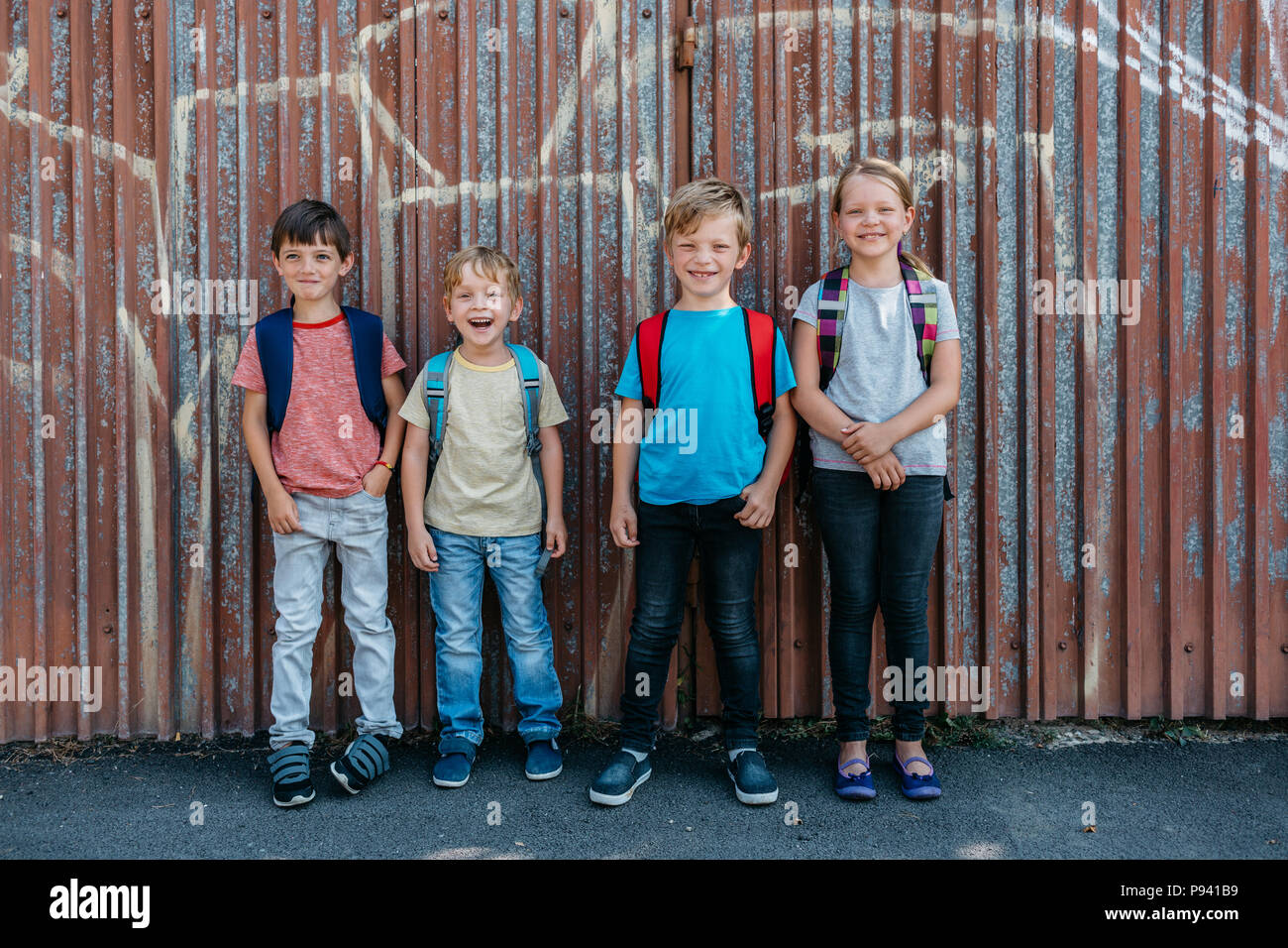 Portrait of young students having fun together on the way to school. Smiling schoolmates standing outside school. - Stock Image
