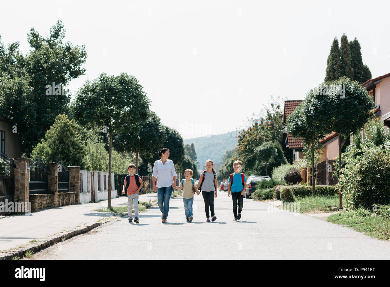 Mother and her children on the morning way to school. A group of primary students walking to school with an adult. - Stock Image