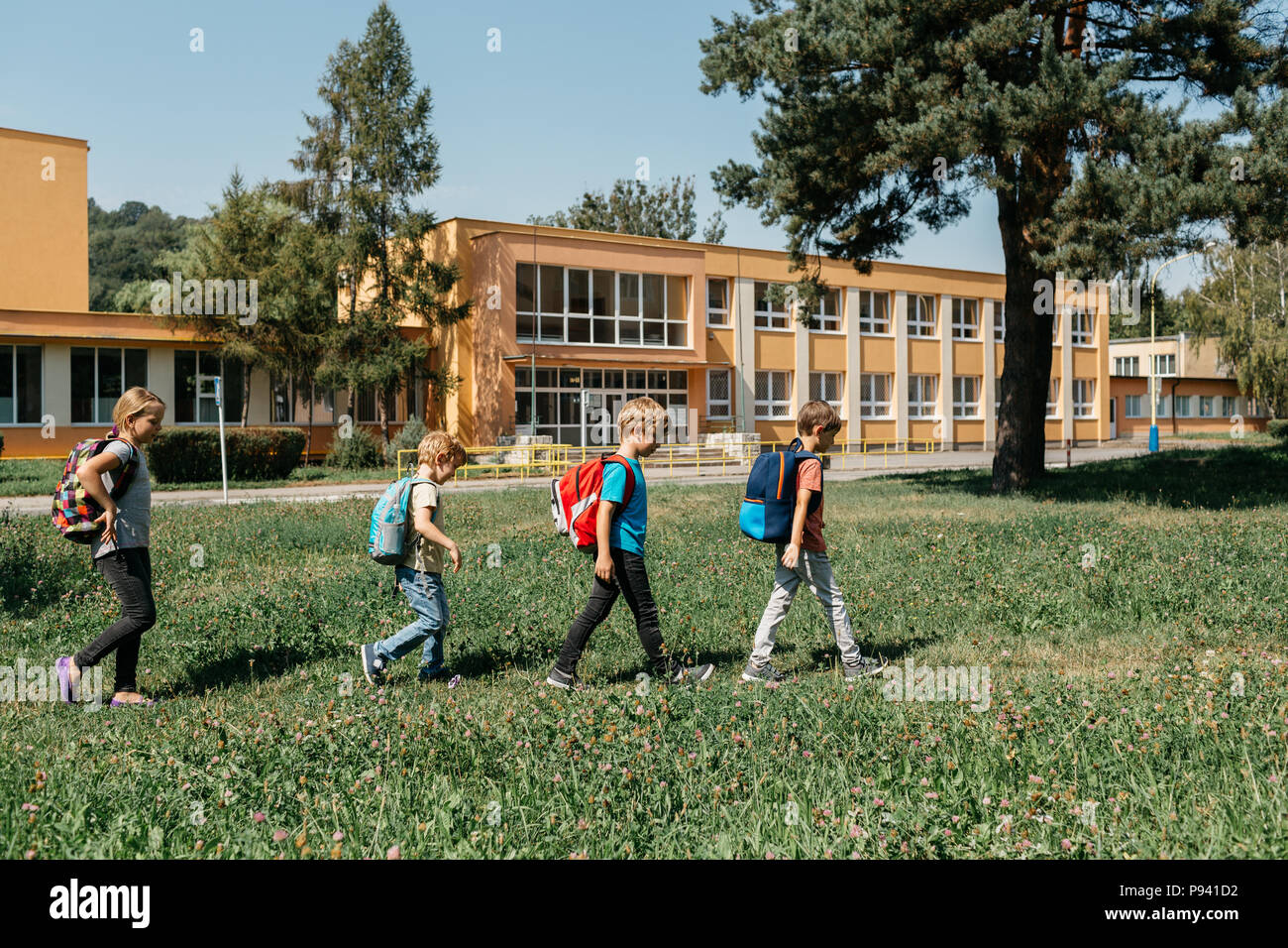 Back to school - children passing by school one after another. Young students walking in line to school on a sunny morning. - Stock Image