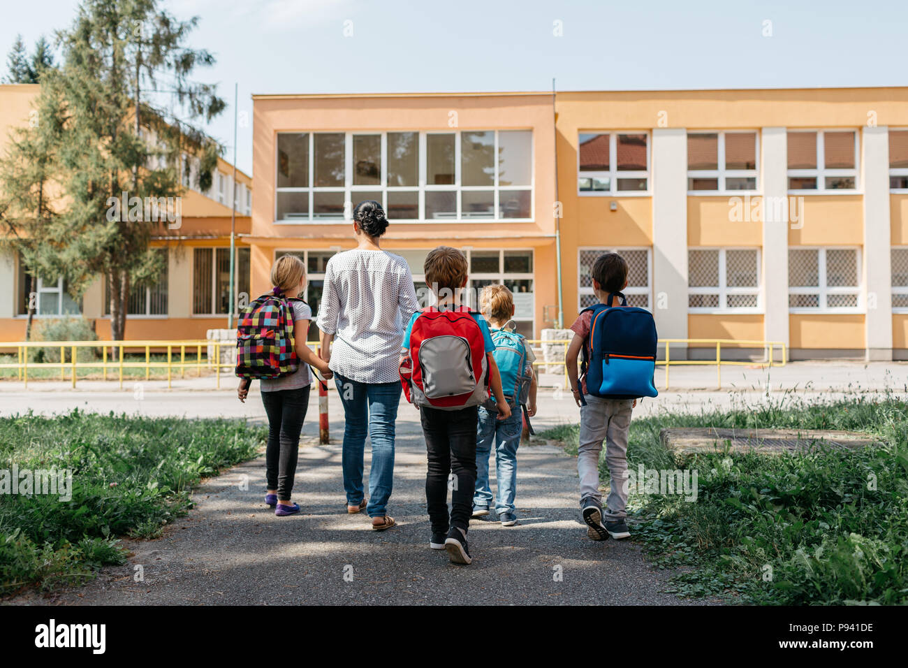 Children on the way to school with an adult supervision. Rear view of a group of children walking to school accompanied by a parent volunteer. - Stock Image
