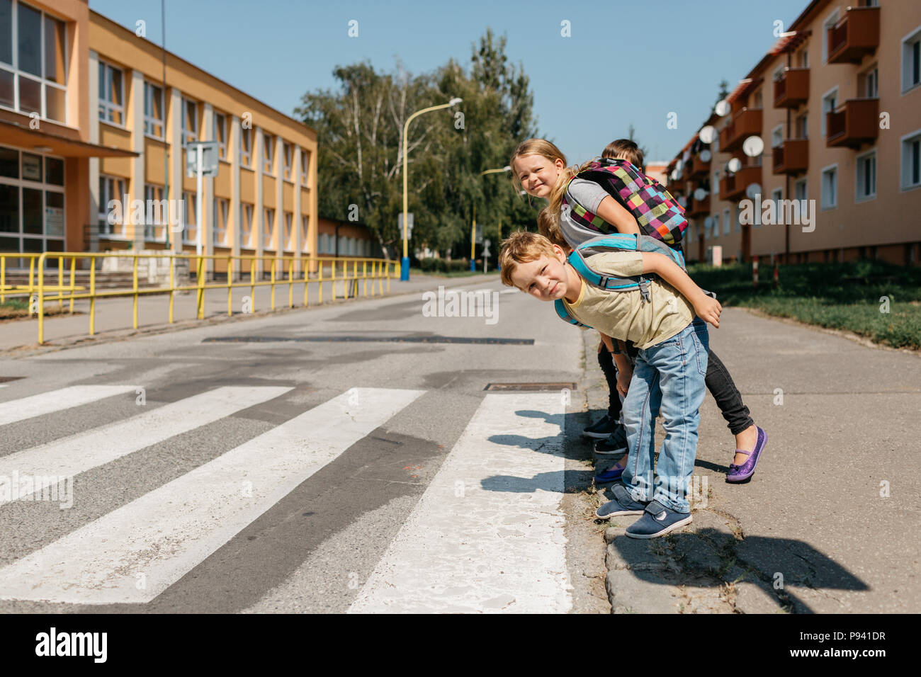Schoolmates at a crosswalk looking right and left before crossing. Children at a zebra crossing looking around and trying to cross a road. - Stock Image