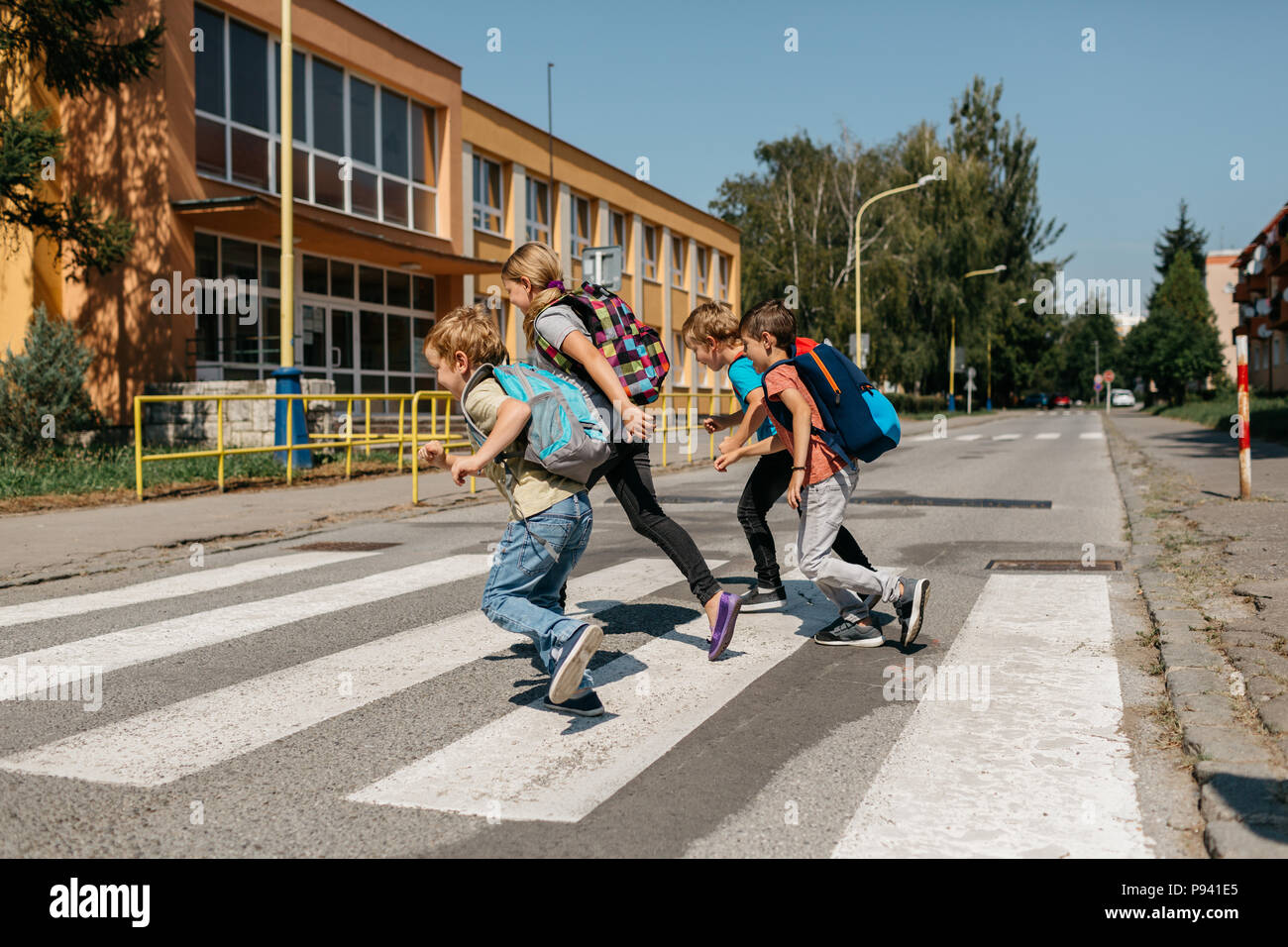 School children running across a street at a crosswalk. Group of primary students rushing to school. - Stock Image