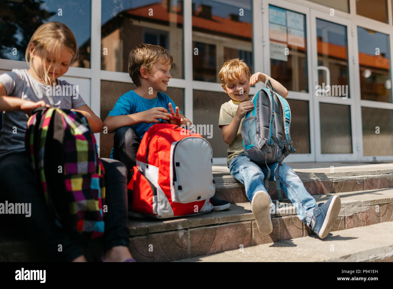 Cheerful school children during a break. Smiling children with schoolbags sitting on stairs outside school. Stock Photo