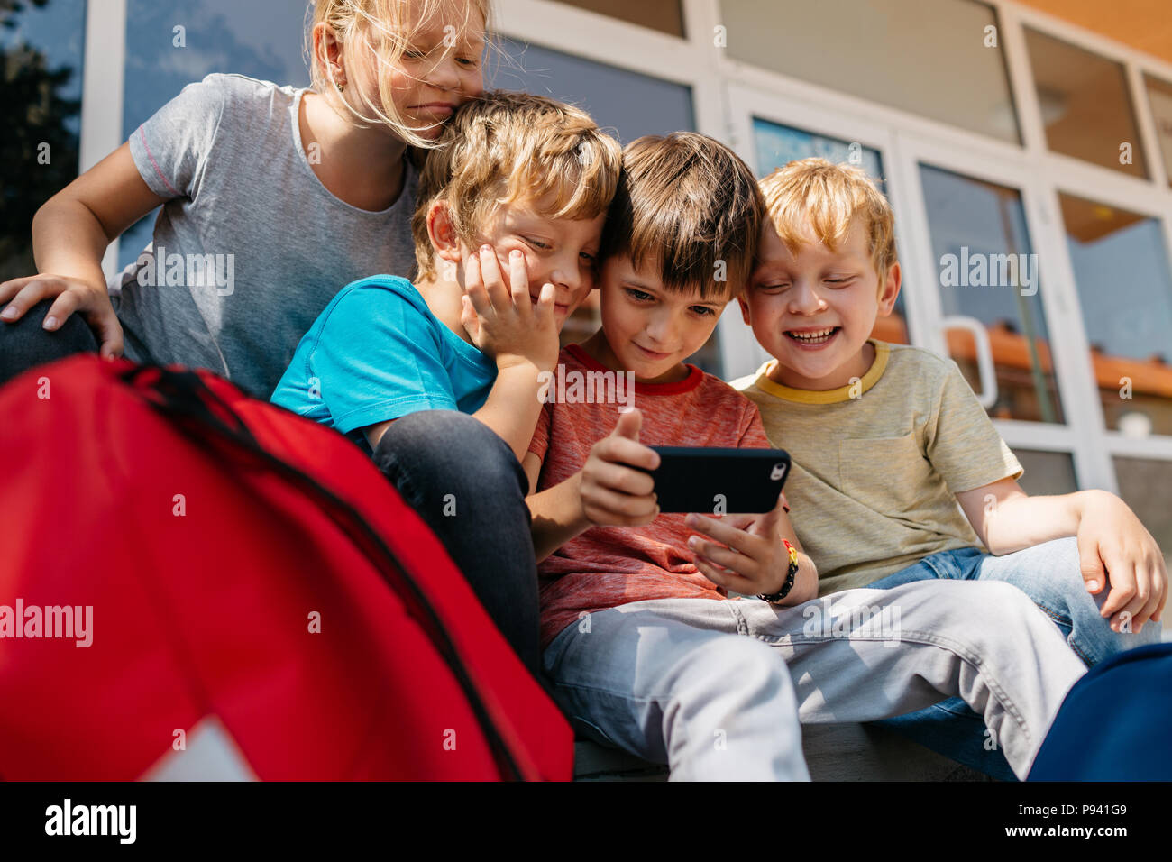 Young students playing with a mobile phone. Children having fun taking a selfie outside of school. Stock Photo