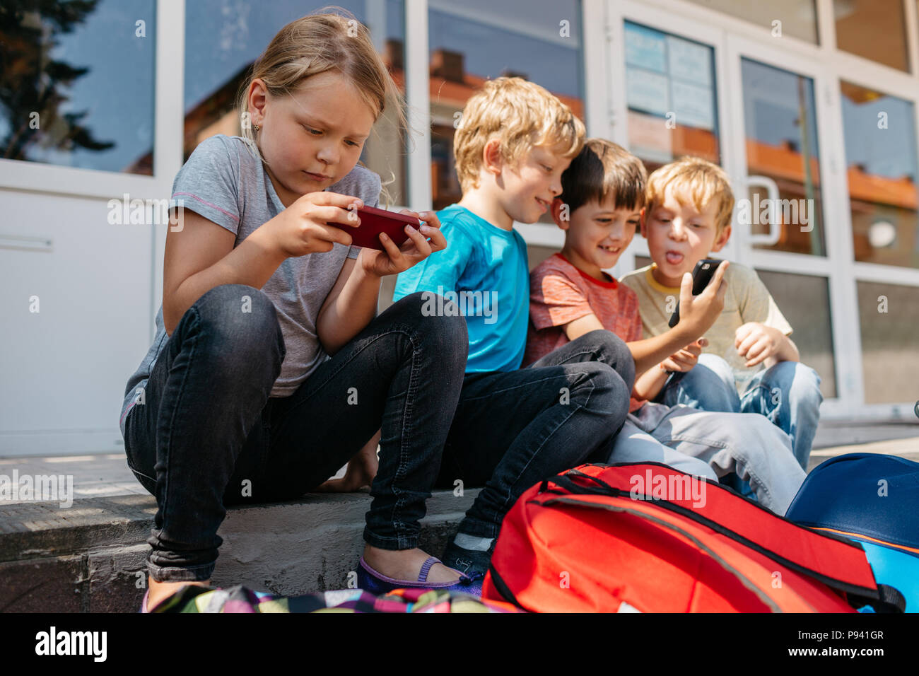 Kids sitting on stairs in front of school web browsing. Schoolchildren having fun playing with mobiles during a break. - Stock Image