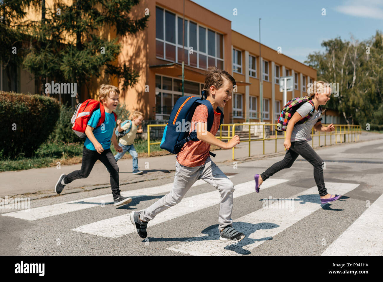 Group of laughing classmates rushing out of school crossing road. Happy children running across a road at a pedestrian crossing. - Stock Image