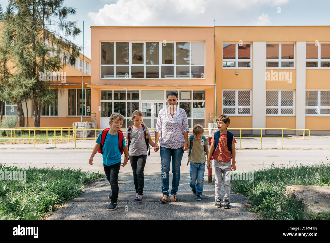 Children going home from school and talking to their mother. Young students walking away from school accompanied by a parent. - Stock Image