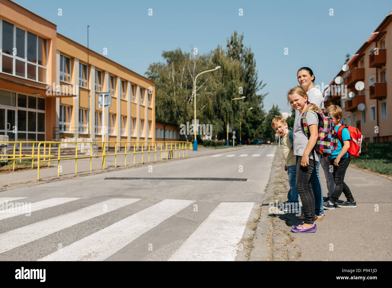 Mother walking to school with her children teaching them road safety. Children on their way to school waiting at a crosswalk. - Stock Image