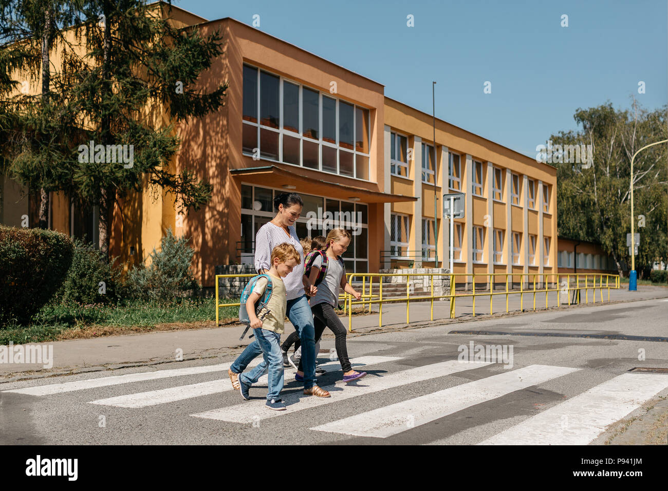Road safety - children crossing a road accompanied by an adult. Mother picking her children up from school. - Stock Image