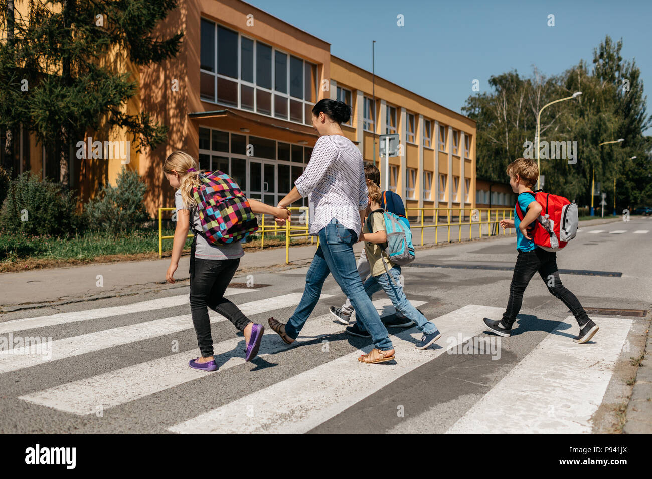 Back to school - a group of children walking across a zebra crossing with an adult. Rear view of children and their mother crossing a street. - Stock Image