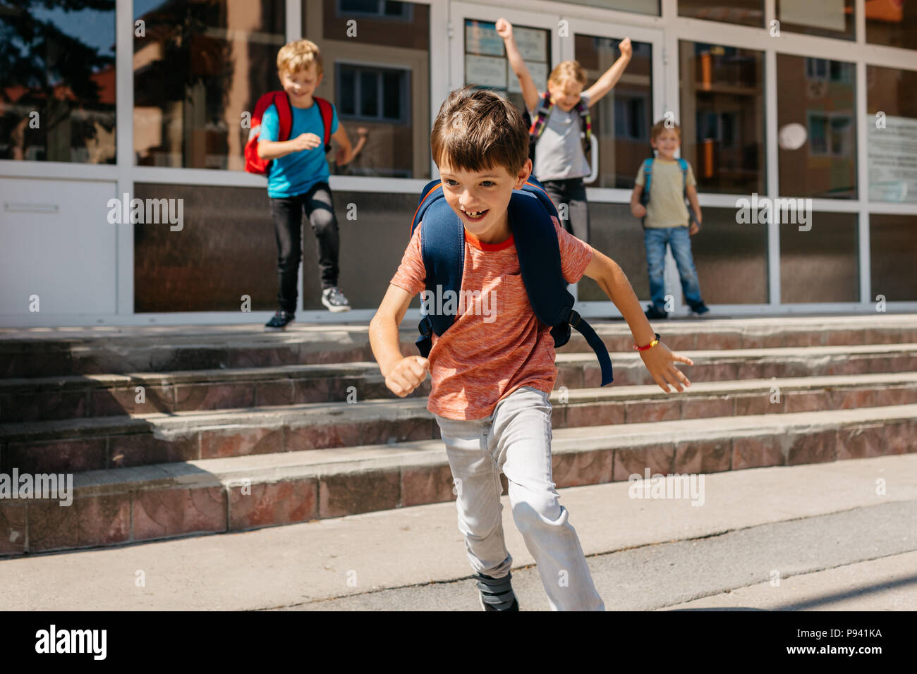 Happy children running away from school. Last day of school - portrait of a cheerful child running away from school. - Stock Image