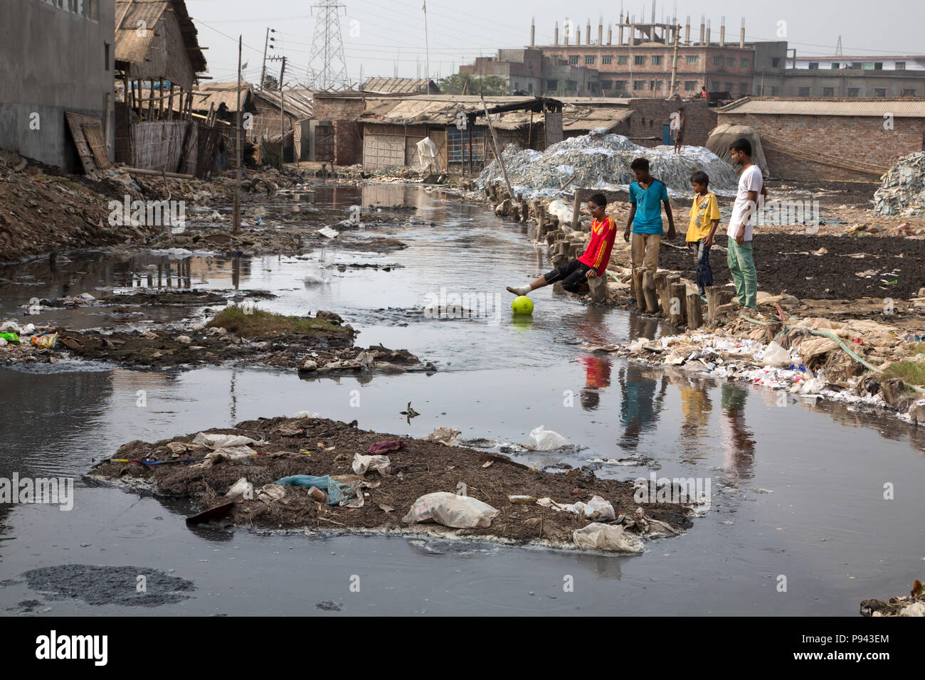 Young men playing in polluted river in Hazaribagh, Dhaka, Bangladesh - Stock Image