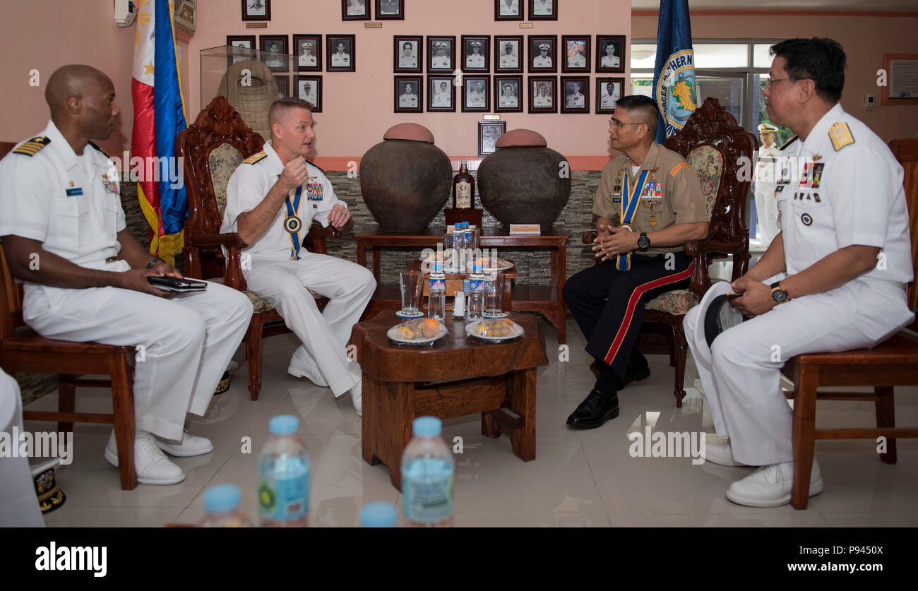 180709-N-OU129-043 SAN FERNANDO CITY, Philippines (July 9, 2018) Rear Adm. Joey Tynch, Commander, Task Force 73 (center-left) and Capt. Lex Walker, Commodore, Destroyer Squadron 7 (left), participate in an office call with Philippine Lt. Gen. Emmanuel Salamat, Commander, Northern Luzon Command (center-right), and Philippine Commodore Nichols Driz, Commander, Naval Forces Northern Luzon, during Maritime Training Activity (MTA) Sama Sama 2018. The week-long engagement focuses on the full spectrum of naval capabilities and is designed to strengthen the close partnership between both navies while  Stock Photo