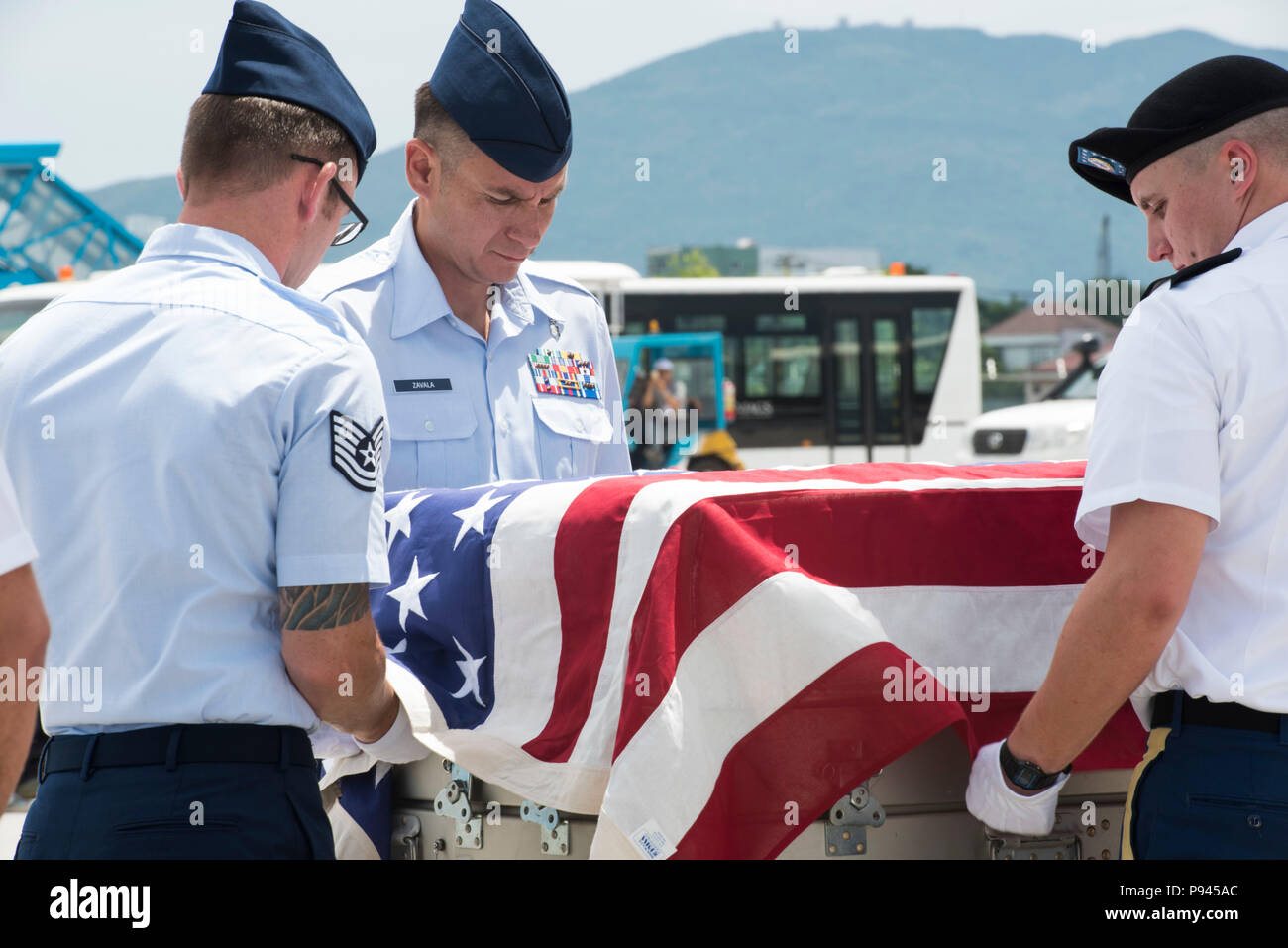 U.S. service members assigned to the Defense POW/MIA Accounting Agency (DPAA), drape a transfer case with the American flag during a repatriation ceremony, Da Nang, Socialist Republic of Vietnam, July 8, 2018. The ceremony was conducted in support of DPAA's mission to provide the fullest possible accounting of our missing personnel to their families and the nation. (U.S. Navy photo by Mass Communication Specialist 2nd Class Claire Farin) - Stock Image