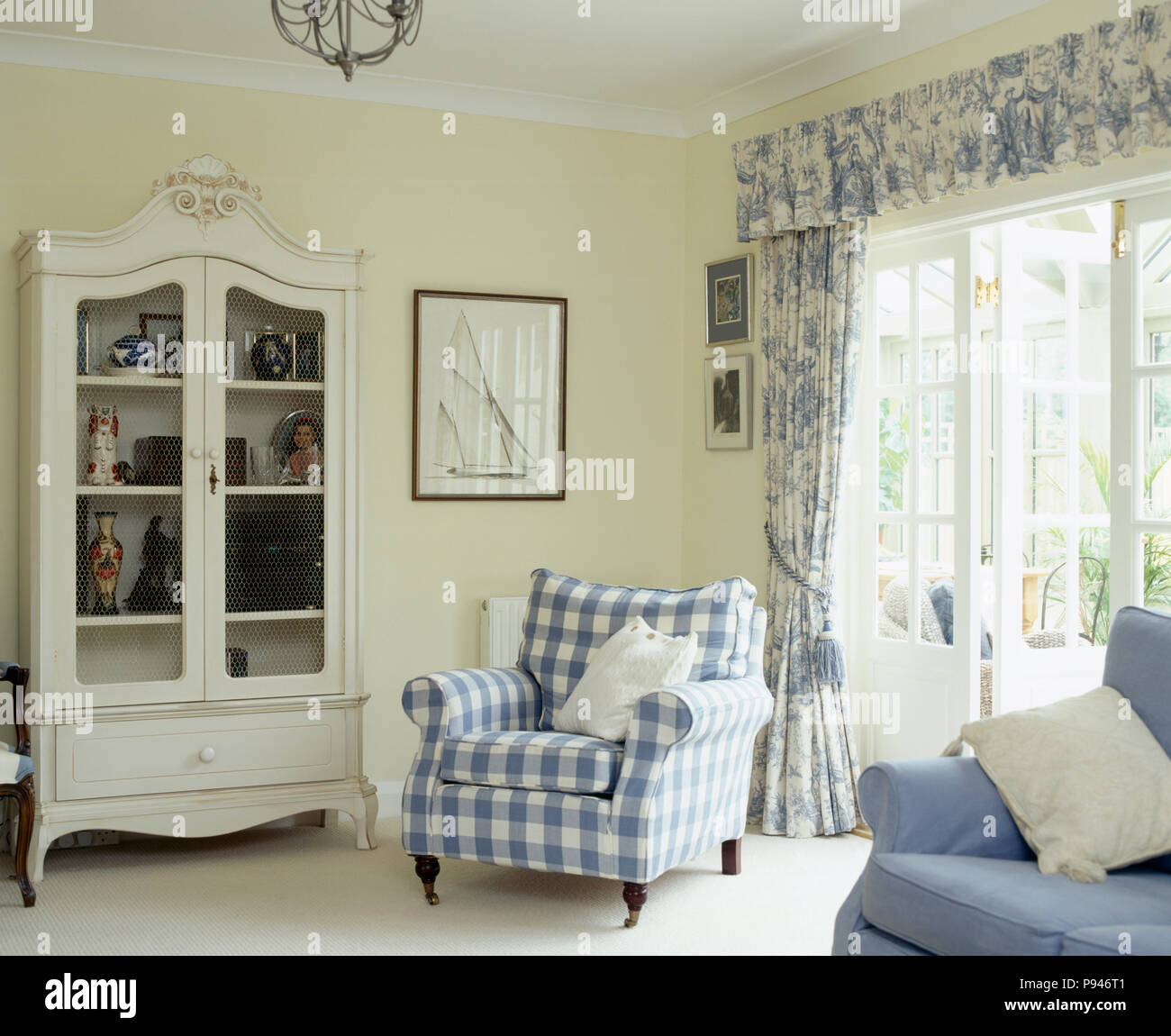 White glass-fronted cupboard and blue checked armchair in ...
