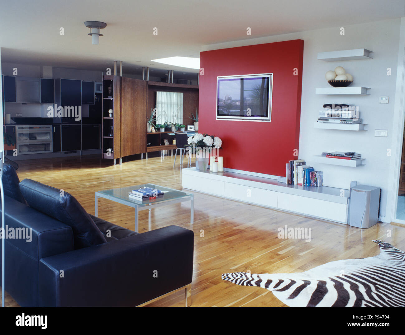 Black leather sofa and wooden flooring in large open-plan ...