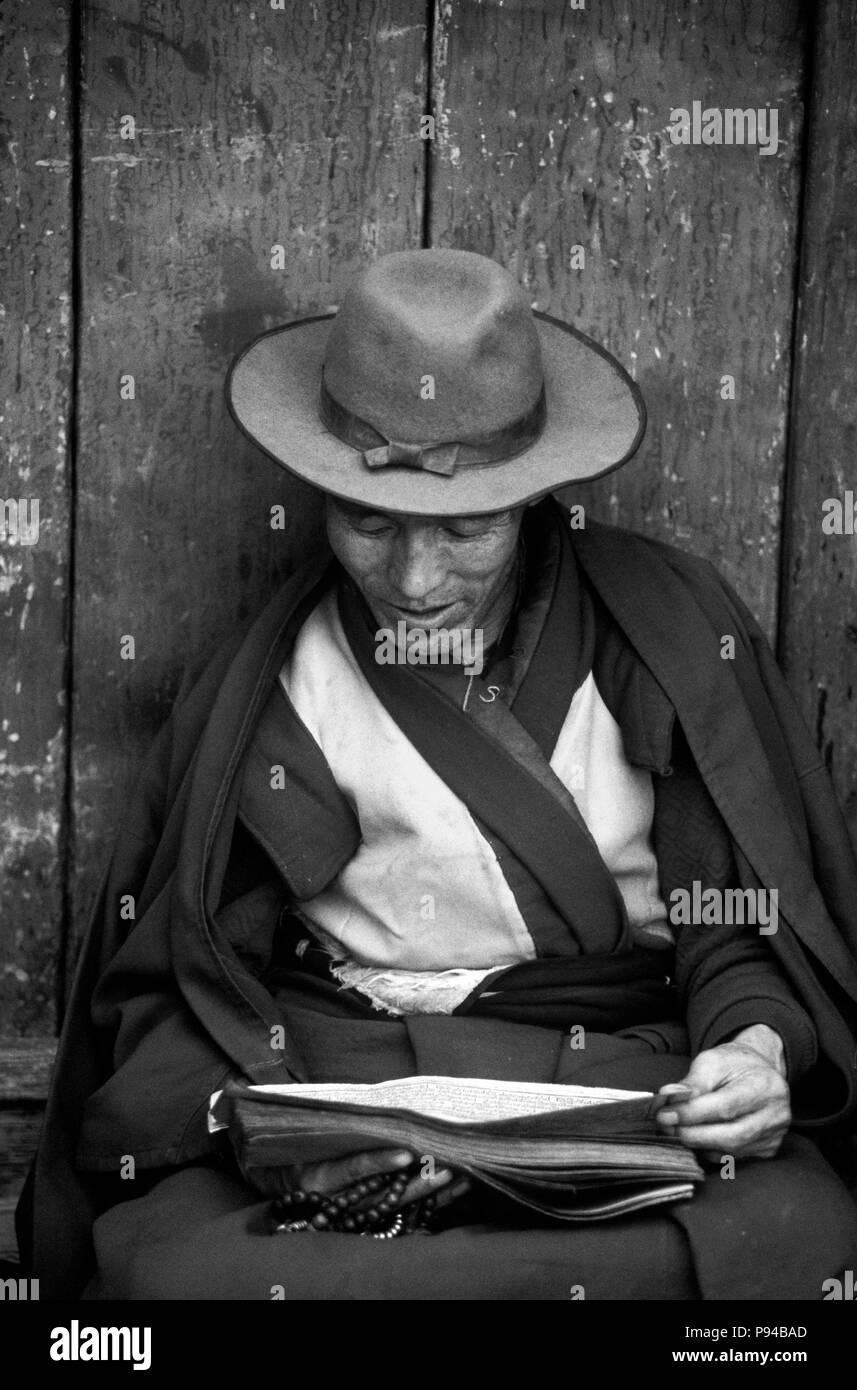 A TIBETAN BUDDHIST MONK reads the SCRIPTURES on the BARKHOR (Tibetan Bazaar) - LHASA, TIBET - Stock Image