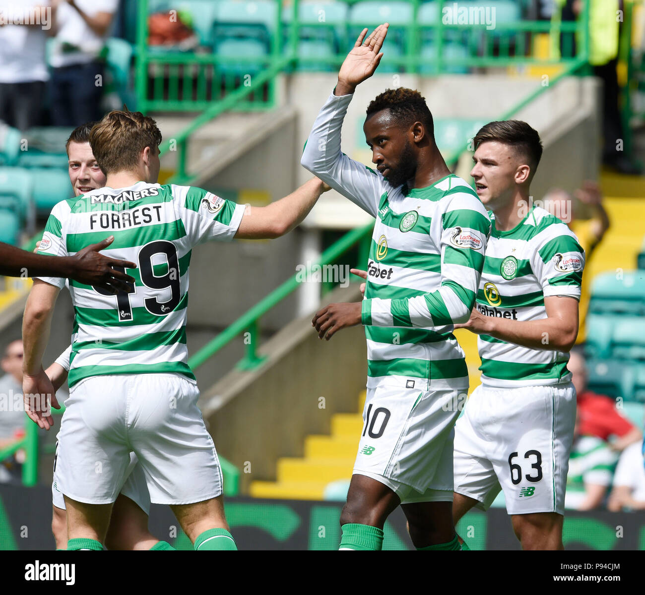 Celtic's Moussa Dembele celebrates with team mates Celtic's James Forrest and Celtic's Kieran Tierney after scoring the second goal during the pre-season match at Celtic Park, Glasgow. - Stock Image