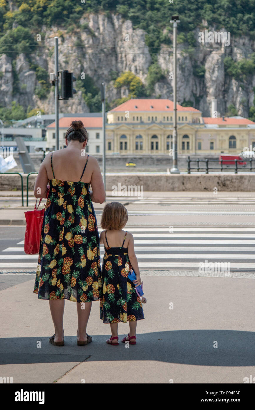 A mother and daughter wearing matching sun dresses wait to cross the road on the banks of the Danube in Budapest, Hungary. - Stock Image