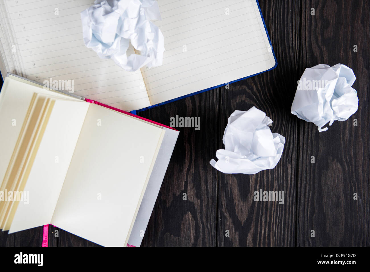 White note pad on a wooden table. near the notepads lies lot crumpled paper. Stock Photo