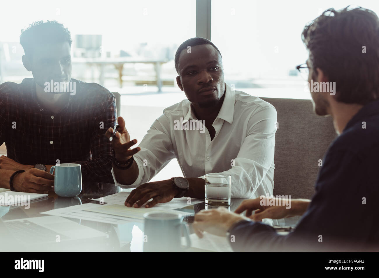 Businessmen discussing work sitting at a conference table in office. Three men in a formal business meeting discussing work. - Stock Image