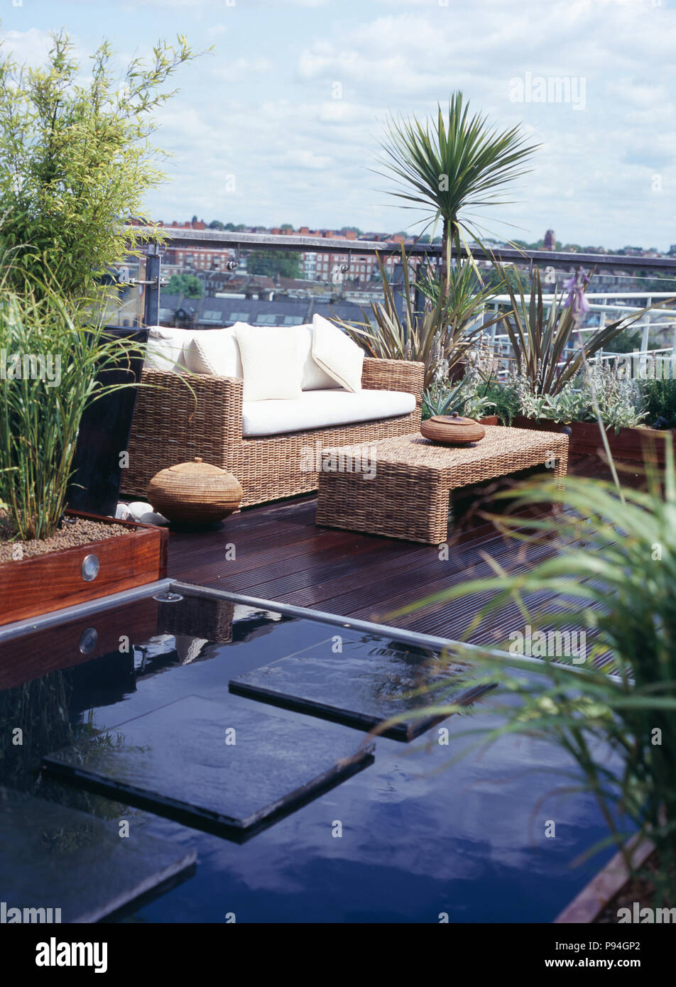Paving Slabs Across Pool On Decked City Roof Garden With Seagrass Table And Matching Sofa With White Cushions Stock Photo Alamy
