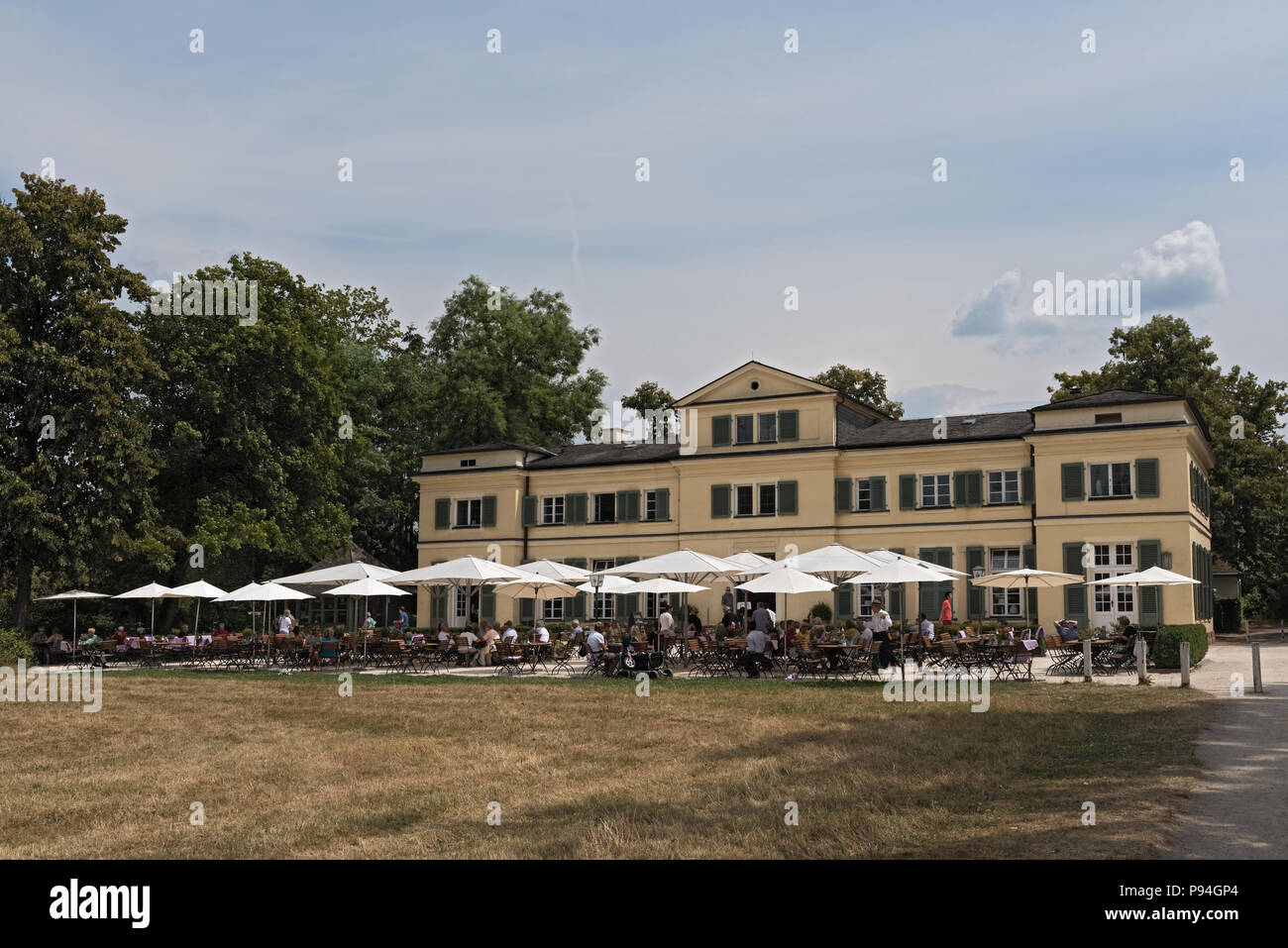 guests on the terrace in front of the restaurant in the historic park Schoenbusch, Aschaffenburg, Germany. - Stock Image