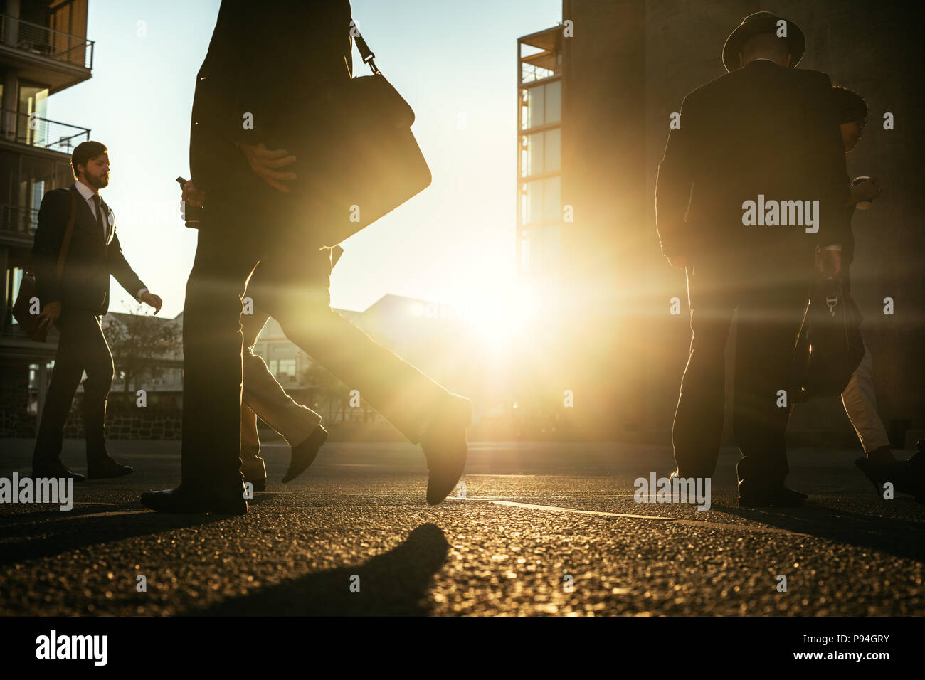 People walking on city street with sun flare in the background. Men commuting to office early in the morning carrying office bags. - Stock Image