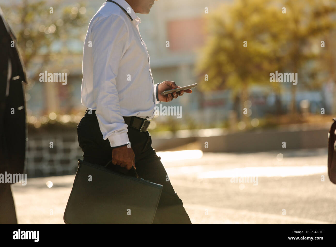 Businessman using mobile phone while commuting to office. Busy office going person walking on street carrying his office bag looking at his mobile pho - Stock Image