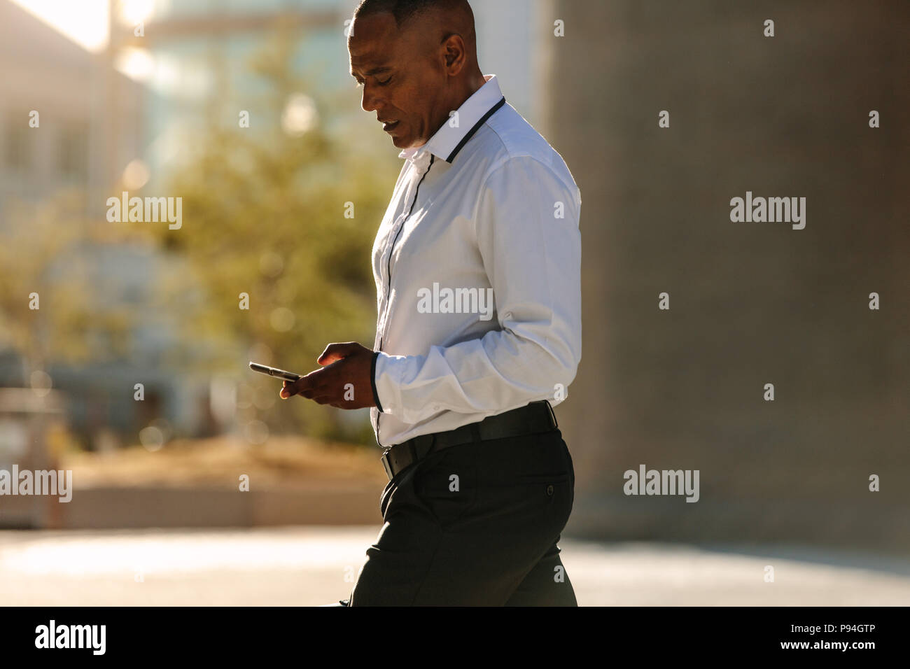 Man in formal clothes looking at his mobile phone while walking on street. Busy office going person walking on street and using his cellphone. - Stock Image