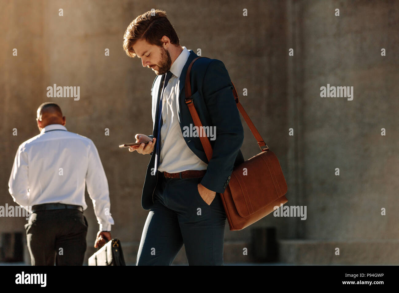 Men in formal clothes commuting to office early in the morning carrying office bags. Businessman using mobile phone while walking on city street to of - Stock Image