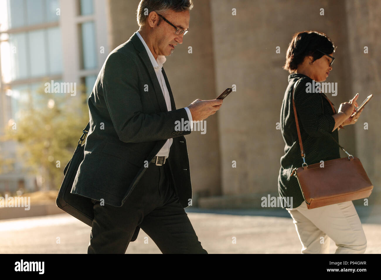 Man and woman using mobile phone while commuting to office on a city street. Business people checking their mobile phone while walking to office showi - Stock Image