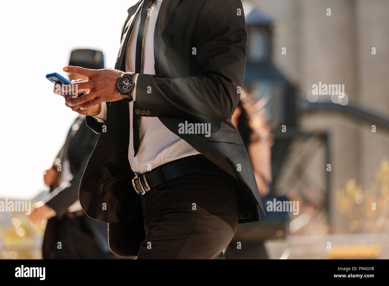 Mid section of a businessman using mobile phone while walking on city street. People commuting to office in the morning busy with their mobile phones. - Stock Image