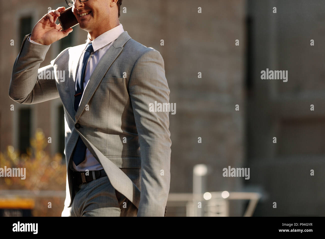 Businessman talking over mobile phone while walking to office in the morning. Man walking on city street to office busy talking on his mobile phone. - Stock Image
