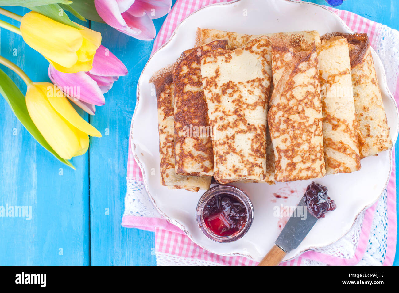 Homemade traditional pancakes with jam for spring carnival. Russian breakfast. Bright flowers of tulips. Blue background. Free space for text or a postcard. - Stock Image