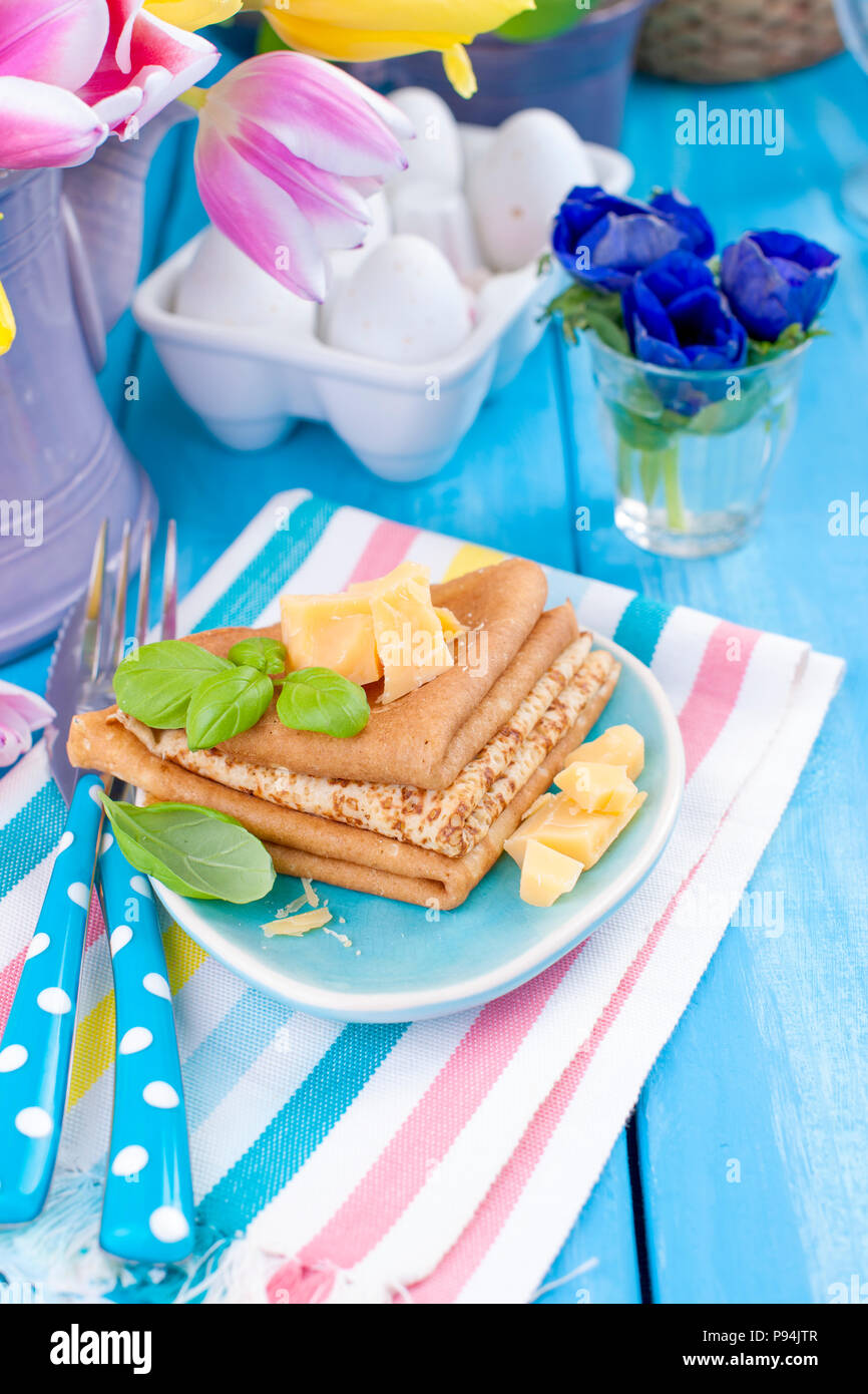 Homemade traditional pancakes with parmesan and basil for spring carnival. Italian breakfast. Bright flowers of tulips. Blue background. A free place for text or a postcard. - Stock Image
