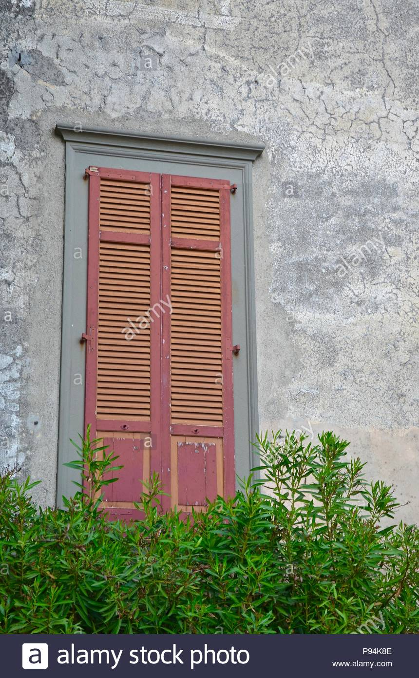 Closed window in a medieval building near Lake d'Iseo in Lombardy, Italy, balcony, conifers, wall, scene, background, iron, grey, red, green, daylight - Stock Image