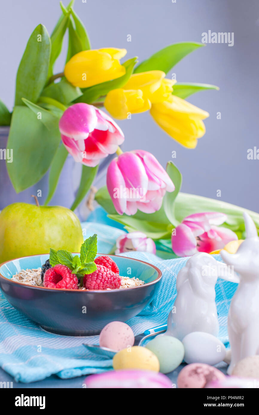 19afd6479ea87 Delicious spring breakfast on a background of gray stone. Bouquet of fresh  tulips. Small and large colored Easter eggs. Oatmeal, coffee, fresh berries.