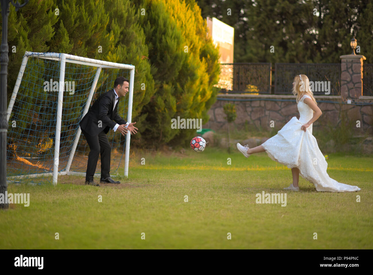 Wedding bride and groom playing football  soccer game bridegroom love marriage marrying couple - Stock Image
