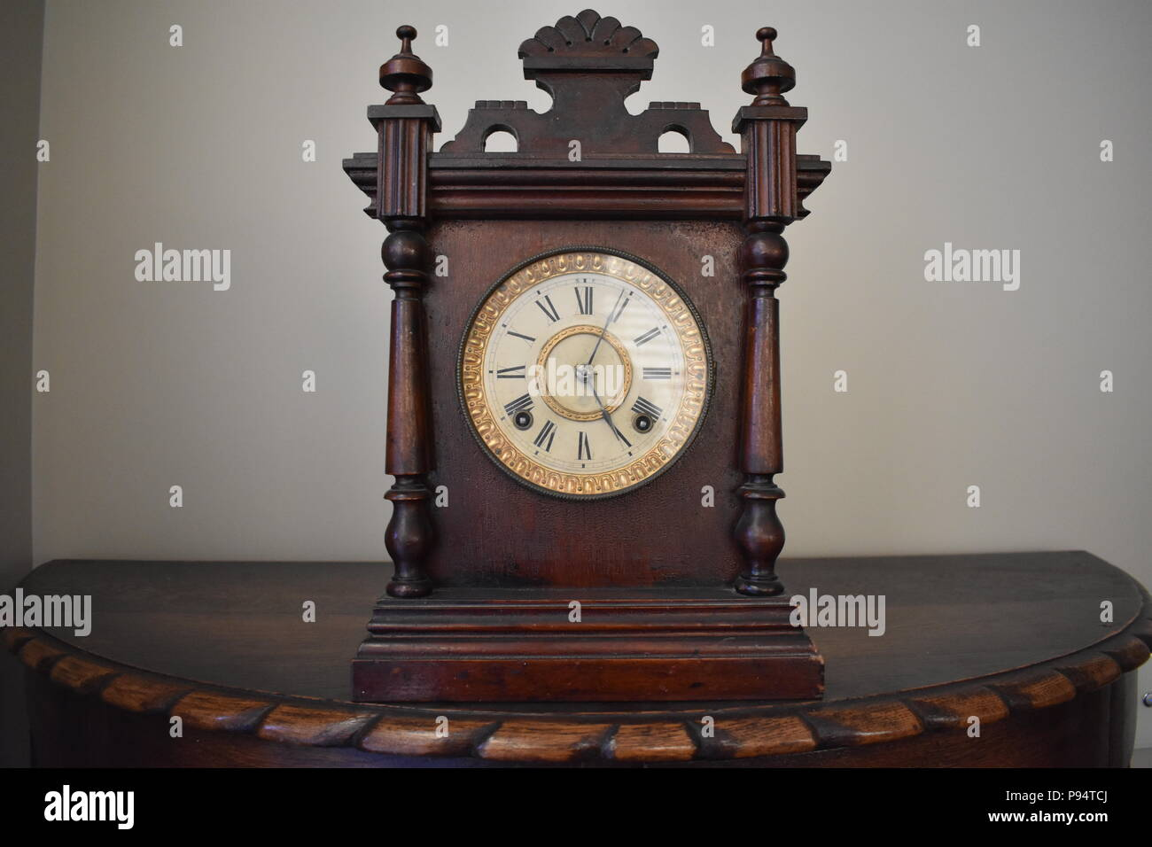 Old wooden clock on mantle piece - Stock Image