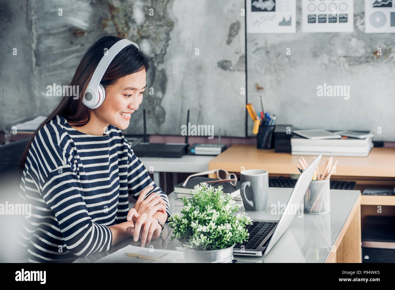 Young asian casual businesswoman arm on desk rest pose with laptop computer and listening music via headphone and think about work ,work at home with  - Stock Image