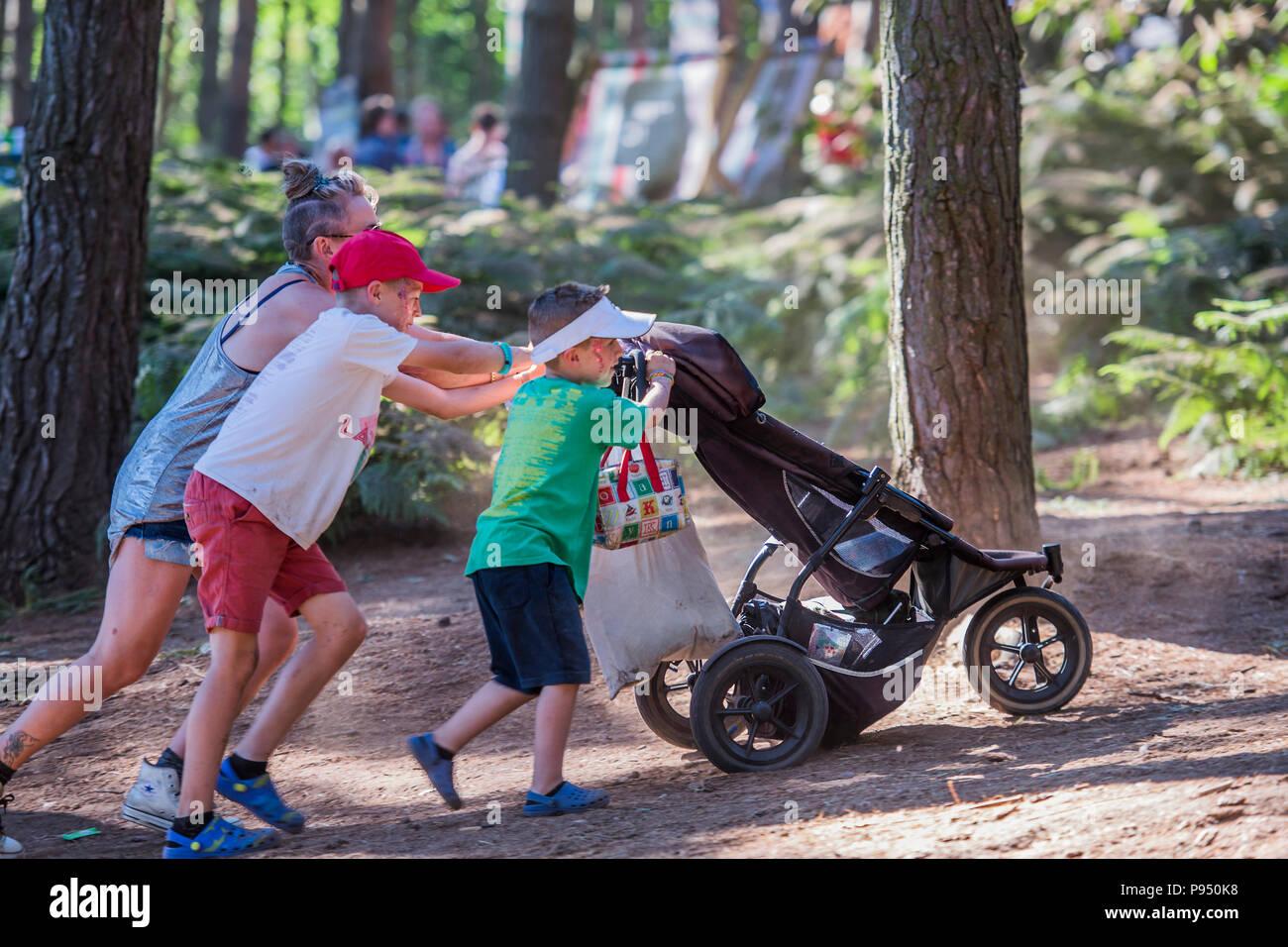 Hard work pushing a buggy up the dusty hill - The 2018 Latitude Festival, Henham Park. Suffolk 14 July 2018 - Stock Image