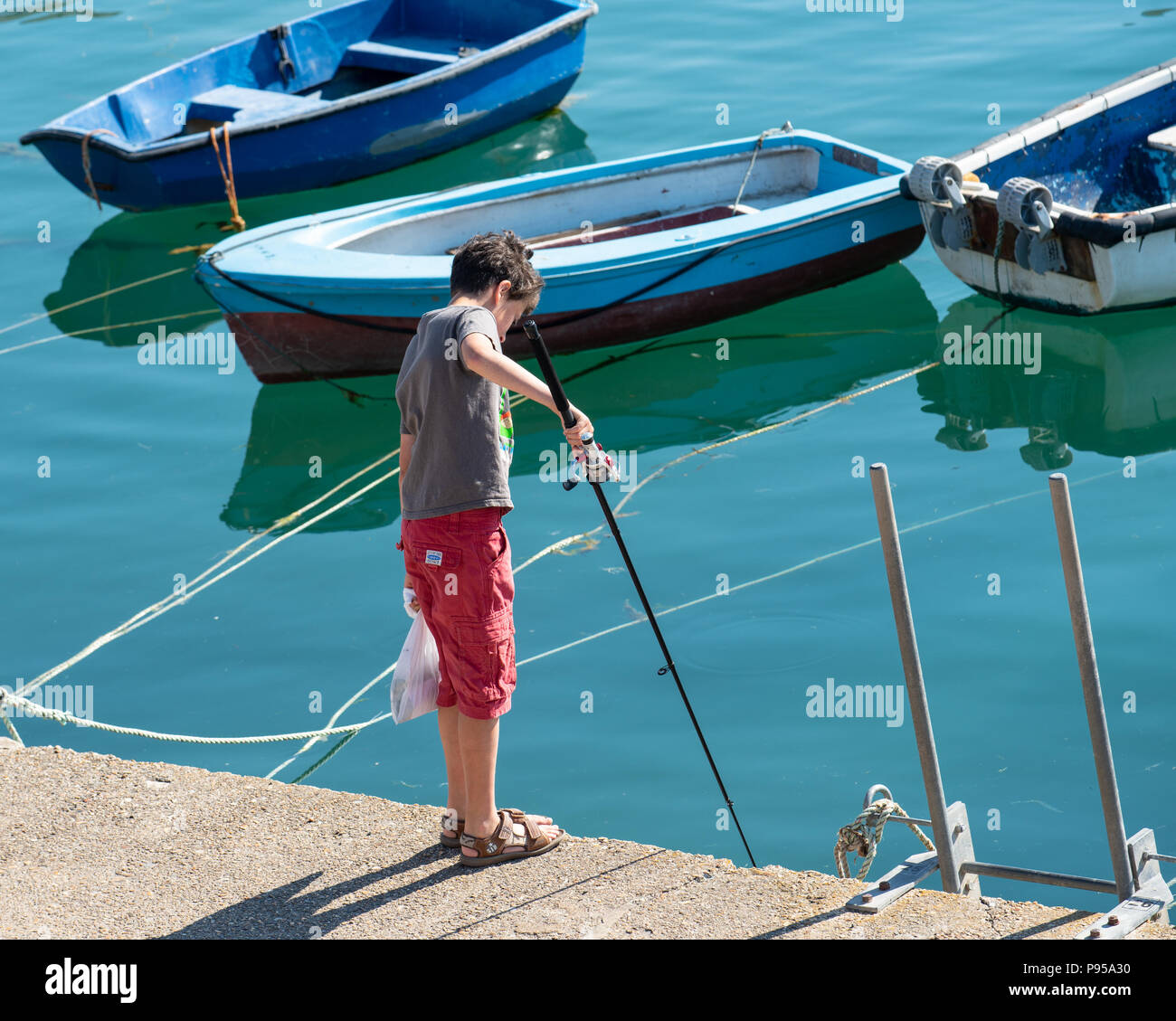 Lyme Regis, Dorset, UK. 15th July 2018.  UK Weather: A very hot and sunny St Swithin's Day in Lyme Regis. A boy with fishing rod.  The scorching hot temperatures are set to contune with temperatures reaching 30 degrees in many parts of the UK again today as the heatwave continues. Credit: Celia McMahon/Alamy Live News. - Stock Image