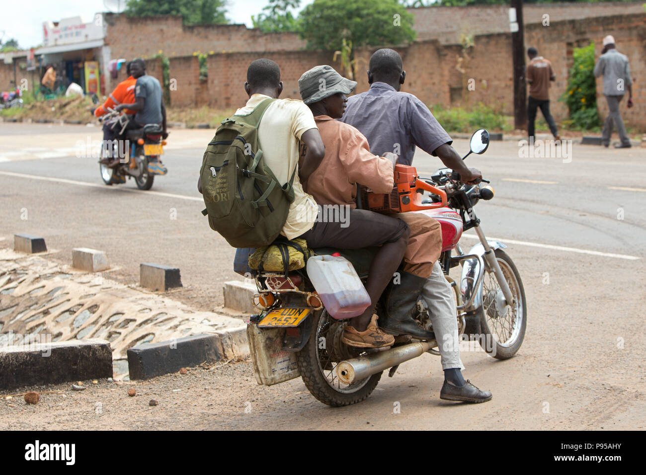 Kamdini, Uganda - Street scene with people and motorcycles. Three men ride a motorcycle. - Stock Image