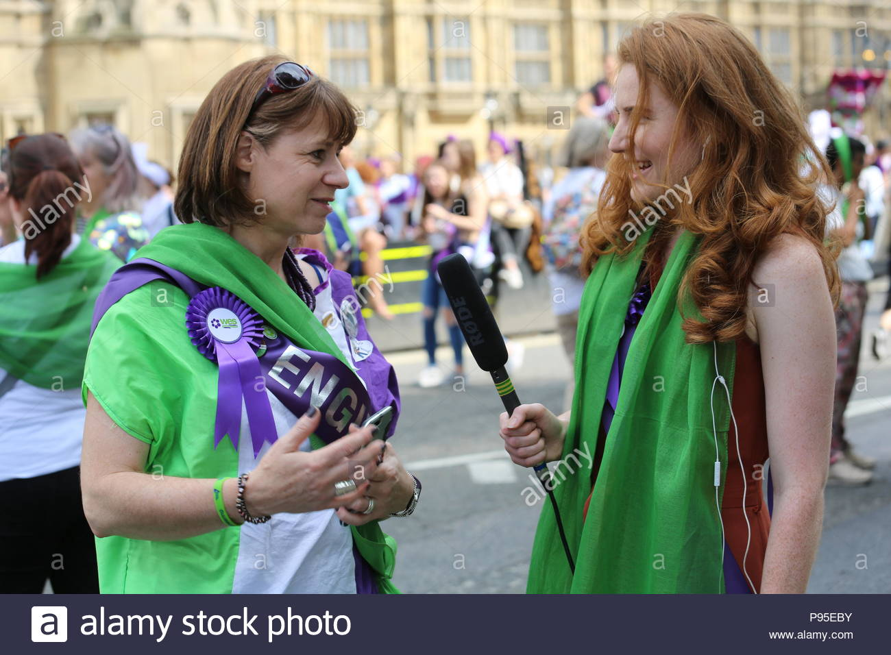A woman is interviewed at the end of a march to Westminster in honour of suffragettes who won the vote in 1918. Stock Photo