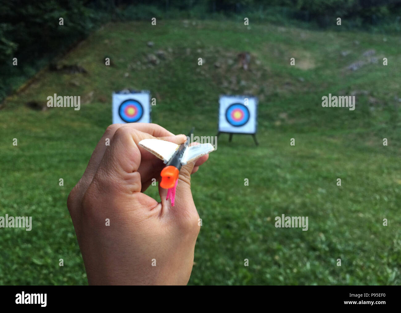 Hand holding an arrow with two targets in the background - Stock Image